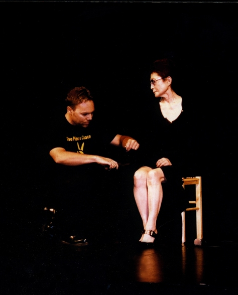Ian Ayres cuts a piece of Yoko Ono's black dress.Photo © 2003 by Eric Elléna