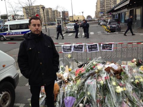 Eric Ellena, at the site of the kosher supermarket siege, pays his respect to the dead. (photo by Ian Ayres)